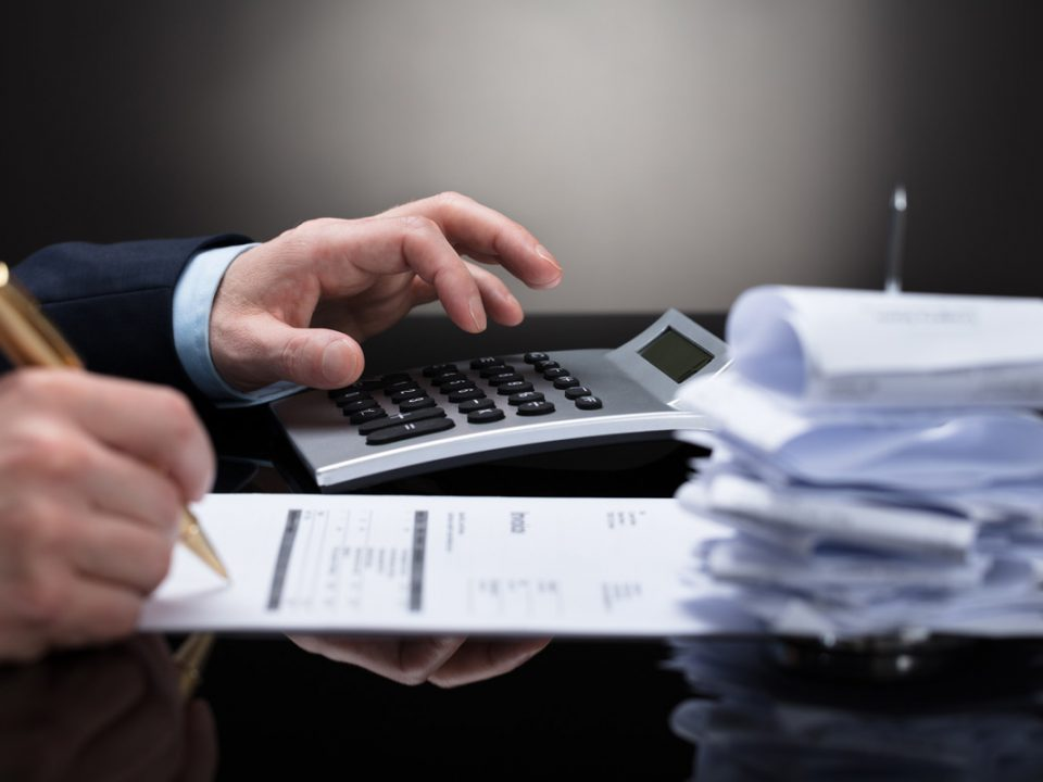 Accountant bookkeeping with receipts and calculator